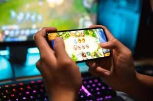 Händer som håller mobil med spel